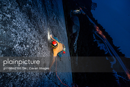 Top view man rock climbing at night above the sea and highway - p1166m2191794 by Cavan Images