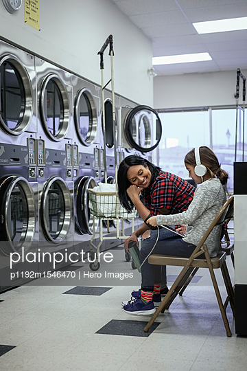 Smiling mother watching daughter with headphones and digital tablet waiting for laundry at laundromat - p1192m1546470 by Hero Images