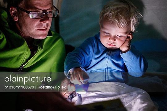 Vater liest Sohn eine Geschichte in einem Zelt vor, Haide, Ummanz, Insel Rügen, Mecklenburg-Vorpommern, Deutschland - p1316m1160579 von Roetting+Pollex
