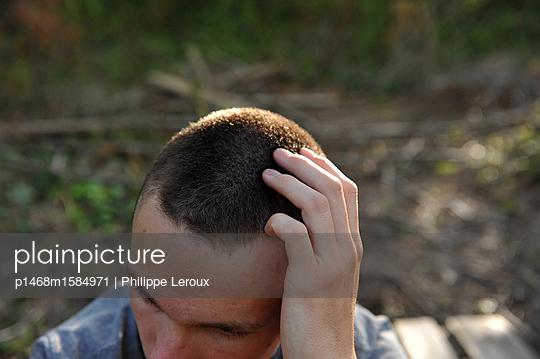 Jugendlicher mit einer Hand auf dem Kopf - p1468m1584971 von Philippe Leroux