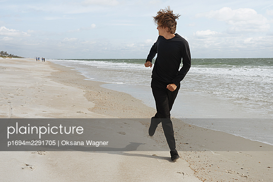 Young man in dark clothes running on the beach and looking back over the shoulder close to the ocean - p1694m2291705 by Oksana Wagner
