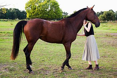 Frau mit Pferd auf der Weide - p1008m1169084 von Valerie Schmidt