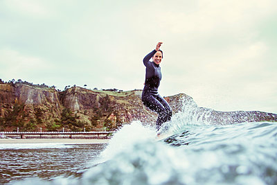 Portrait of happy woman surfing on sea against cloudy sky - p1166m1150449 by Cavan Images
