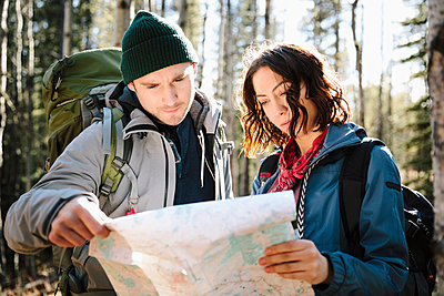 Couple with map hiking in sunny woods - p1192m2093982 by Hero Images