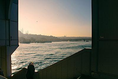 Eine Frau mit Kopftuch blickt, an das Geländer einer Brückenunterführung gelehnt, über den Bosporus bei untergehender Sonne hinweg, eingerahmt von zwei Brückenpfeilern - p1400m1571141 von Bastian Fischer