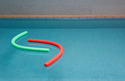 Aqua noodles floating on water of indoor swimming pool - p300m1115253f by Wolfgang Weinhäupl