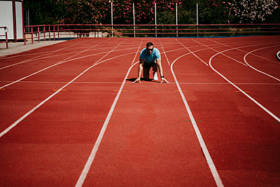 Male athlete in starting position on tartan track - p300m2202502 by Eva Blanco