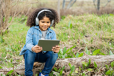 Boy wearing headphones using digital tablet in nature - p300m2266361 by Jose Carlos Ichiro