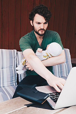 Father with baby boy using laptop while sitting on chair against wall - p426m1506266 by Maskot
