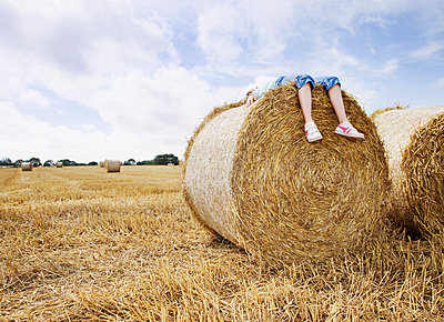 Girl laying on bale of hay - p6417821f by Anthony Lee