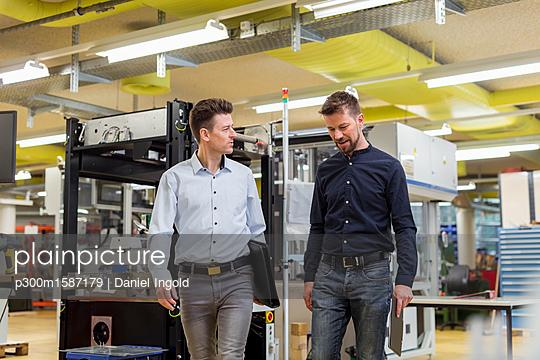 Two men talking in factory - p300m1587179 von Daniel Ingold