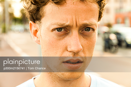 Portrait of sceptical young strawberry blonde man - p300m2156741 by Tom Chance