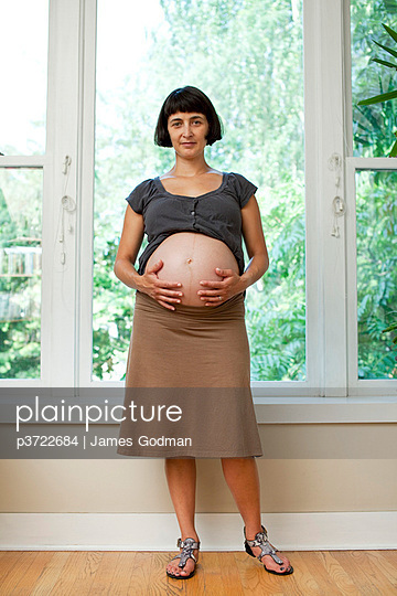 Portrait of pregnant woman standing by window - p3722684 by James Godman