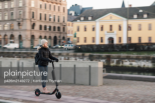 Full length of teenage girl riding e-scooter on street in city - p426m2149272 by Kentaroo Tryman