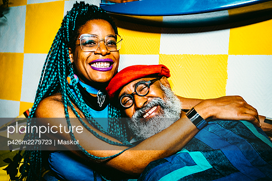 Portrait of smiling mid adult woman hugging senior male friend at apartment - p426m2279723 by Maskot