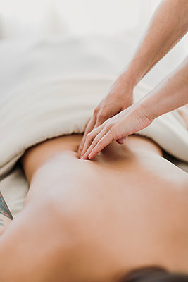 A massage therapist works on a female patient's back - p1166m2107025 by Cavan Images