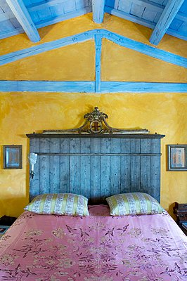 Contrasting colours and styles; wooden ceiling painted pale blue and marbled, ochre walls as backdrop for stained headboard of double bed - p1183m997619 by Tremolada, Emilio