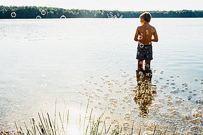 Boy in a lake surrounded by soap bubbles - p300m2004023 von Jana Mänz