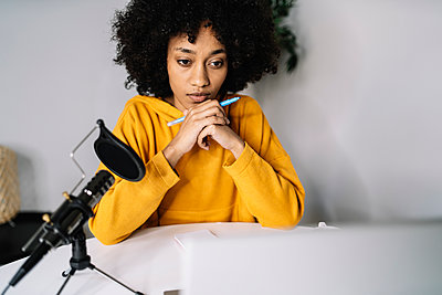 Concentrated woman with felt tip pen podcasting at home - p300m2275457 by COROIMAGE