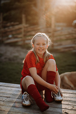 Smiling girl putting football shoes on - p312m2208134 by Anna Johnsson