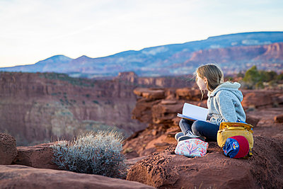 Mädchen sitzt auf einem Felsen - p756m1584535 von Bénédicte Lassalle