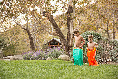 Two brothers having a sack race, County Park, Los Angeles, California, USA - p924m973944f by David Jakle