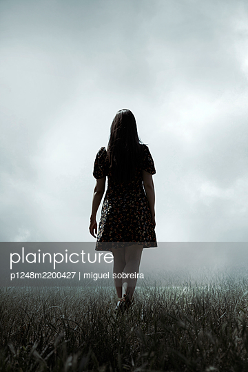 Overcast Sky, Woman walking in Grass  - p1248m2200427 by miguel sobreira