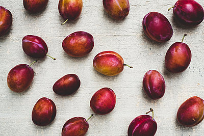 Close up of fresh damsons fruits on grey background. - p1100m2084897 by Mint Images