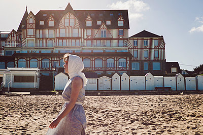 France, Brittany, Saint Cast, Woman in front of beach houses - p1150m2260479 by Elise Ortiou Campion