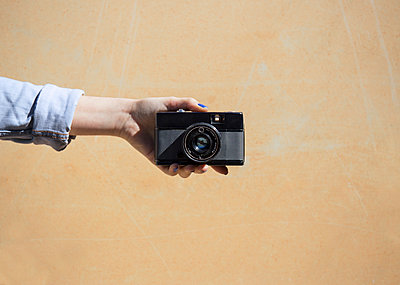 Cropped image of woman holding camera against wall - p1166m1151163 by Cavan Images
