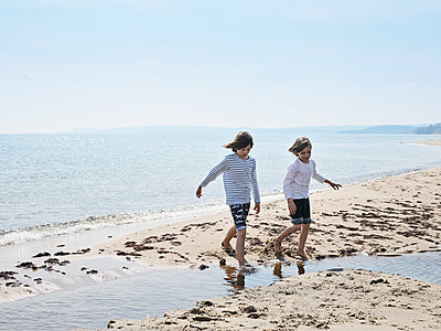 Siblings on a sandy beach at the Baltic Sea, Sweden - p1481m2203868 by Peo Olsson