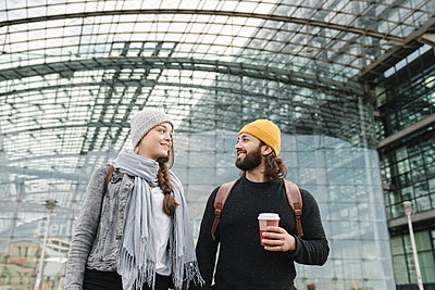 Happy young couple with takeaway coffee at the central station, Berlin, Germany - p300m2155173 by Hernandez and Sorokina