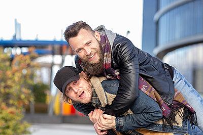 Cheerful gay man piggybacking boyfriend while standing in city - p300m2242803 by Jose Carlos Ichiro