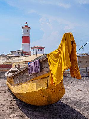 Einbaumboot am Strand und Leuchtturm im Hintergrund - p390m1586511 von Frank Herfort