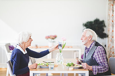 Senior woman showing mobile phone to man while having lunch in nursing home - p426m2018570 by Maskot