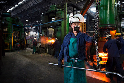 Operative prepares to hook steel billet out of furnace. Team in background using counterblow hammer - p429m875676f by Charlie Fawell