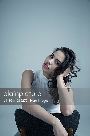 Portrait serious brunette Latina young woman leaning with hand in hair - p1192m1213270 by Hero Images