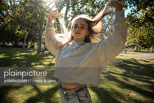 Teenage girl cuts a caper in the park - p1640m2258517 by Holly & John