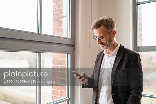 Businessman using cell phone at the window in office - p300m2102944 by Daniel Ingold