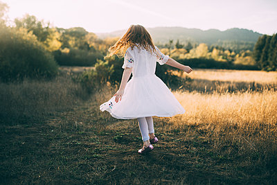 Full length of playful girl wearing white dress while spinning at park - p1166m1530594 by Cavan Images