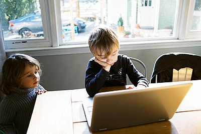 Little boy in morning light sitting at table doing remote school - p1166m2232711 by Cavan Images
