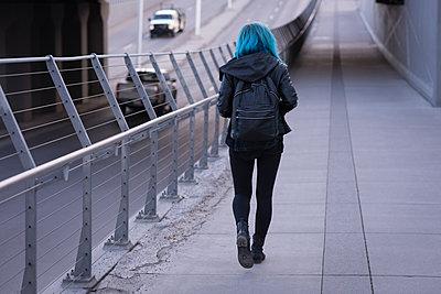 Rear view of stylish woman walking on road  - p1315m1566157 by Wavebreak
