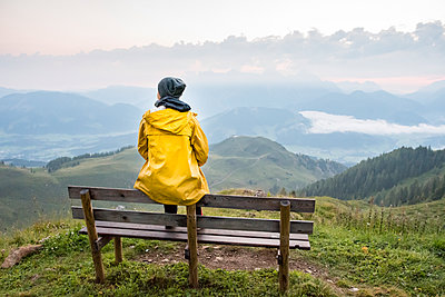 Austria, Tyrol, Fieberbrunn, Wildseeloder, woman sitting on bench with view on mountainscape - p300m2042985 by Petra Silie