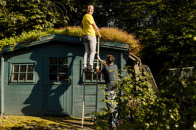 Man standing on ladder supported by son in front of house at back yard - p300m2276961 by Gustafsson