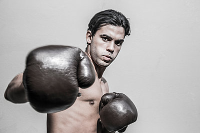 Young man with boxing gloves  - p975m1466272 by Hayden Verry