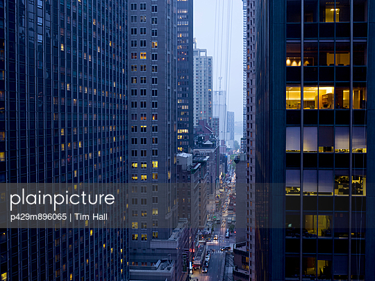Elevated view of rush hour between skyscrapers at dusk - p429m896065 by Tim Hall