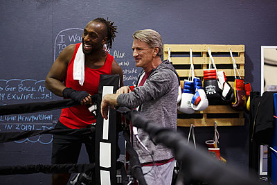 Male boxer and trainer talking in gym - p1192m2033931 by Hero Images