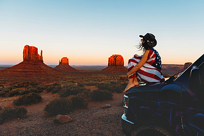 USA, Utah, Woman with United States of America flag enjoying the sunset in Monument Valley - p300m1587158 von Gemma Ferrando