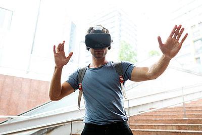 Young man enjoying virtual reality headset at subway station - p300m2221395 by Valentina Barreto