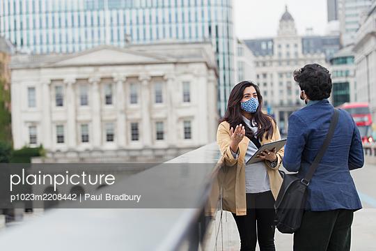 Business people in face masks talking on city bridge, London, UK - p1023m2208442 by Paul Bradbury